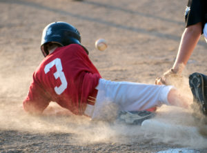 A kid sliding into a base playing baseball